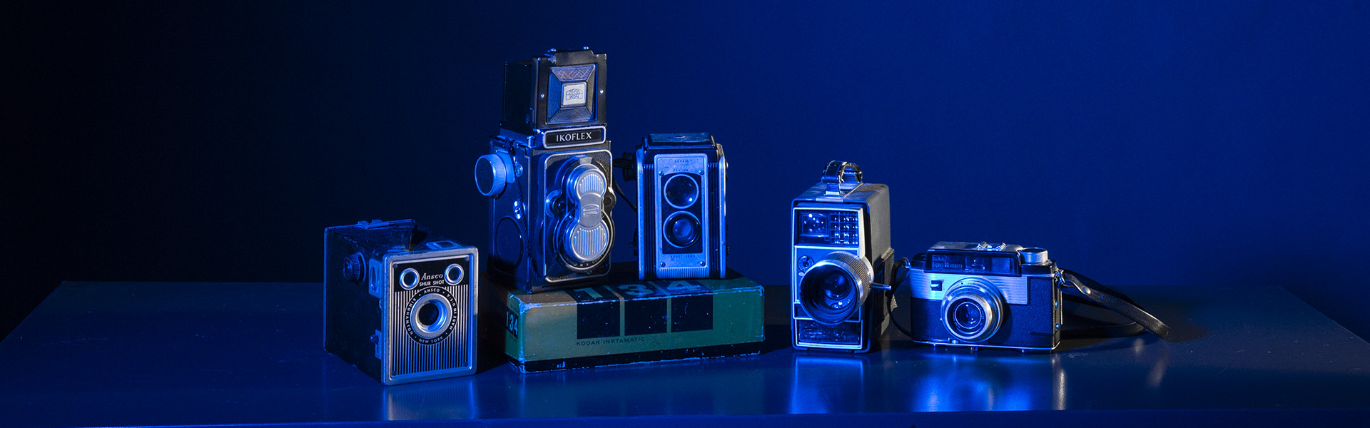 vintage cameras lit with blue gels in studio